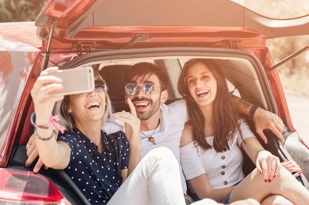 Mujer sentada en la fotografía de toma de tronco de coche a través de teléfono móvil Foto gratis