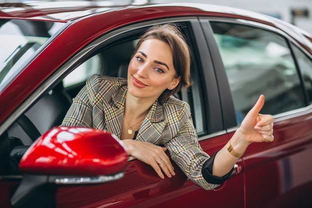 Mujer sentada i coche en un coche showrrom Foto gratis
