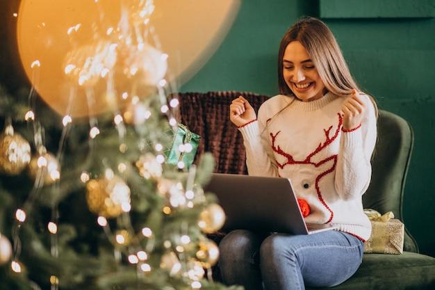 Mujer sentada junto al árbol de navidad y compras en línea de ventas Foto gratis