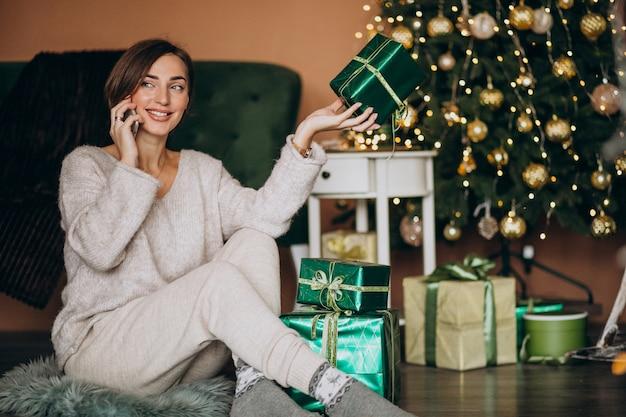 Mujer sentada junto al árbol de navidad y de compras por teléfono Foto gratis