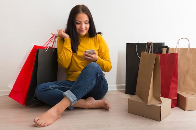 Mujer sentada junto a bolsas de la compra. Foto gratis