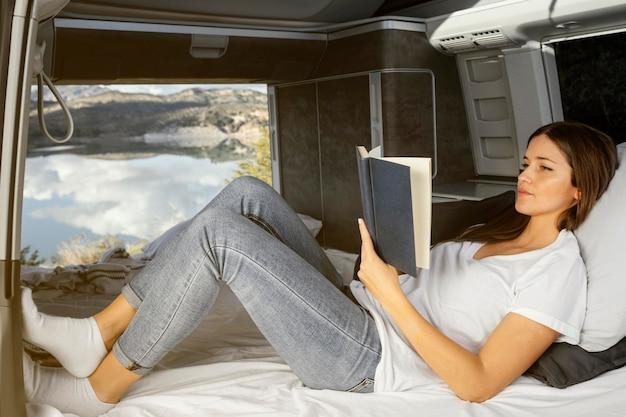 Mujer sentada y leyendo de tiro completo Foto gratis