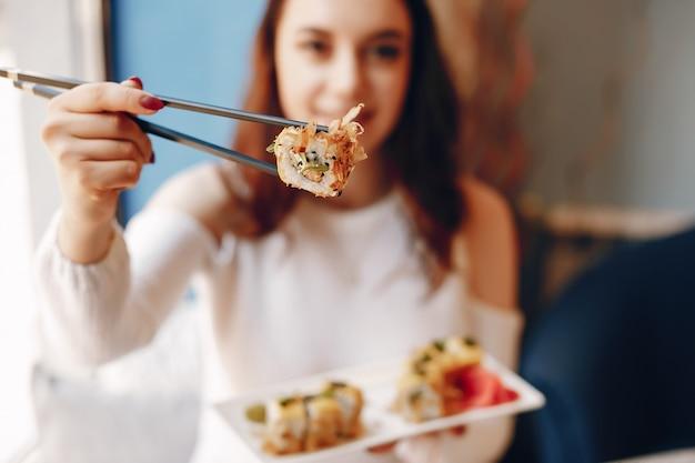 Mujer sentada en la mesa y comiendo sushi en la cafetería Foto gratis