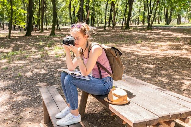 Mujer sentada en una mesa y tomar una foto Foto gratis