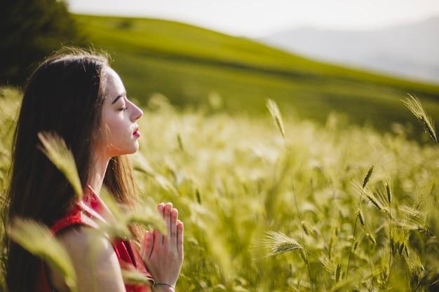 Mujer sentada en la naturaleza y meditando Foto gratis