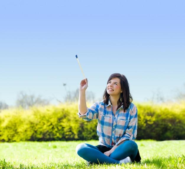 Mujer sentada con un palo Foto gratis