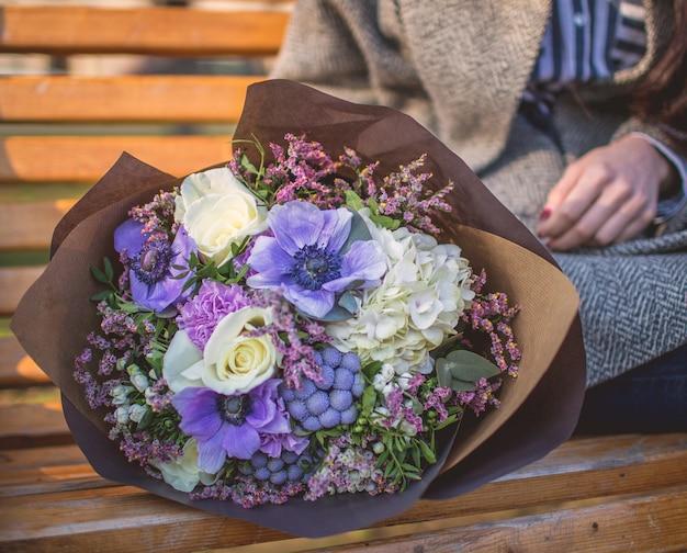 Mujer sentada en el pench con un ramo de flores de papel. Foto gratis