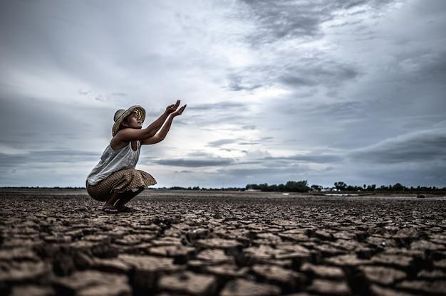 Una mujer está sentada pidiendo lluvia en la estación seca, el calentamiento global Foto gratis