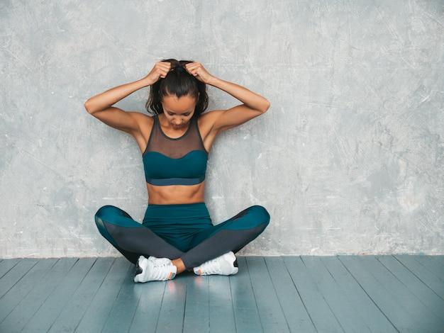 Mujer sentada en el piso en estudio cerca de la pared gris Foto gratis