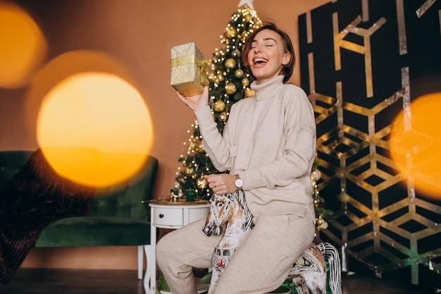 Mujer sentada en una silla pony de madera junto al árbol de navidad Foto gratis