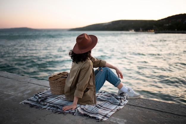 Mujer sentada sobre una manta full shot Foto gratis