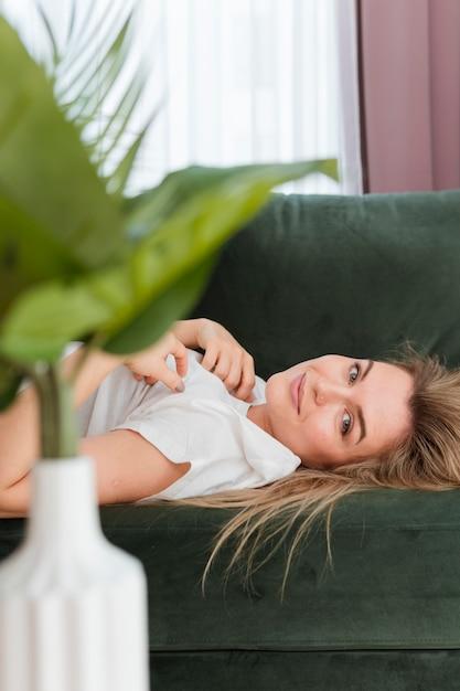 Mujer sentada en el sofá y planta en un florero Foto gratis