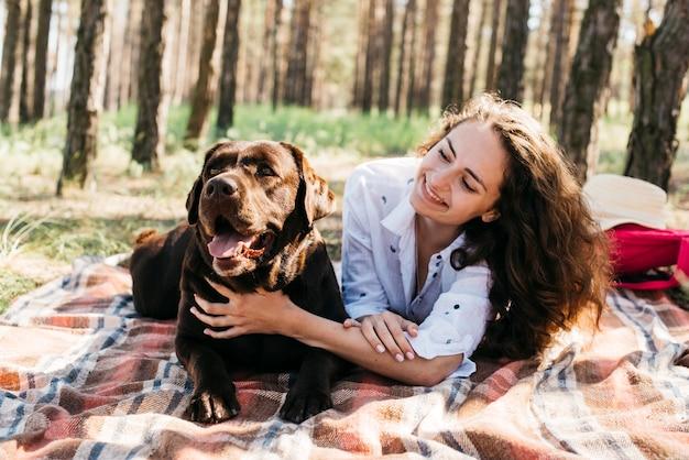 Mujer sentada con su perro en la naturaleza Foto gratis