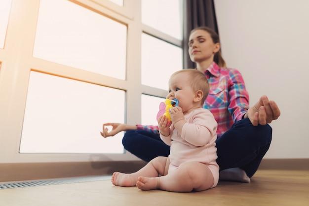 Una mujer está sentada en el suelo con el bebé y meditando. Foto Premium