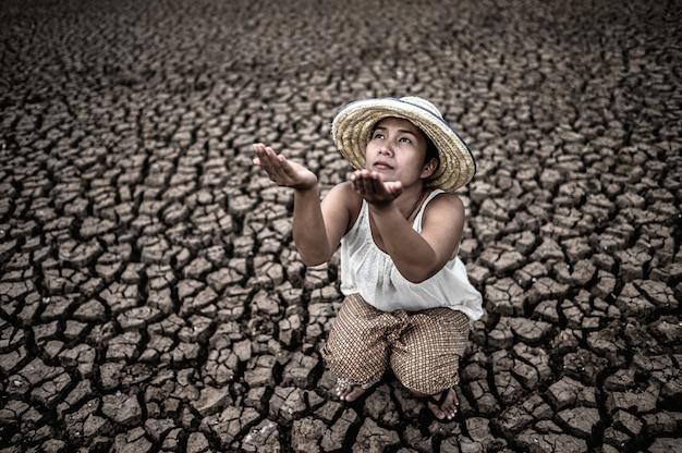 La mujer se sentó mirando al cielo y pidió lluvia en el clima seco, el calentamiento global. Foto gratis