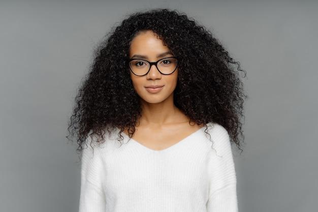 Mujer seria con piel oscura, cabello afro tupido, usa grandes lentes transparentes y suéter blanco suave Foto Premium