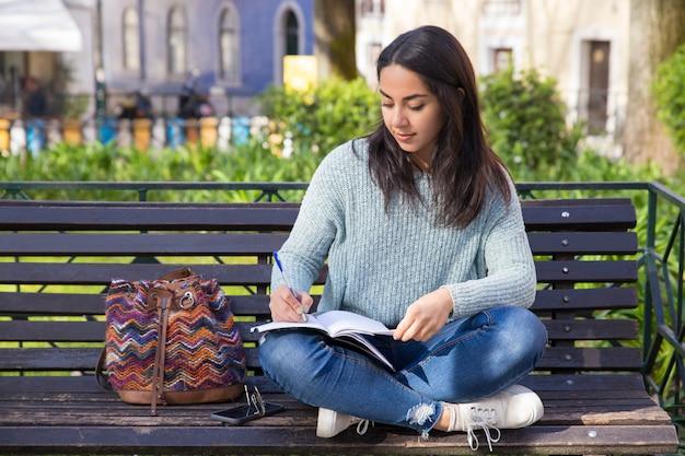 Mujer seria que hace notas y que se sienta en banco al aire libre Foto gratis