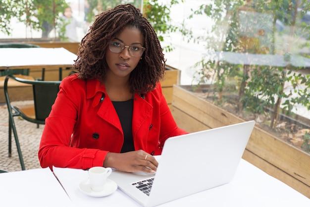 Mujer seria usando laptop y mirando Foto gratis