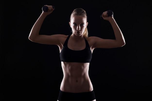 Mujer sexy haciendo ejercicios con mancuernas Foto gratis