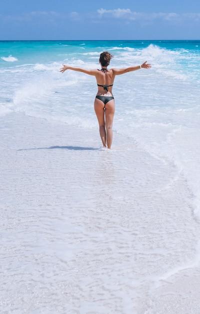 Mujer sexy en traje de baño de pie en el océano Foto gratis