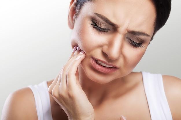 Mujer siente dolor de dientes Foto Premium