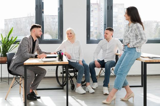 Mujer en silla de ruedas y compañeros de trabajo en la oficina conversando Foto gratis