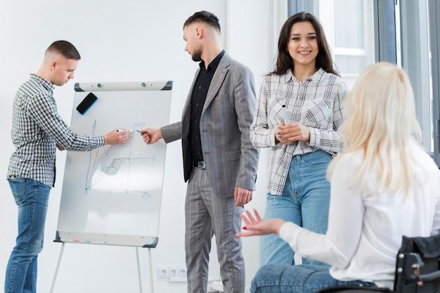 Mujer en silla de ruedas conversando con un colega en el trabajo Foto gratis