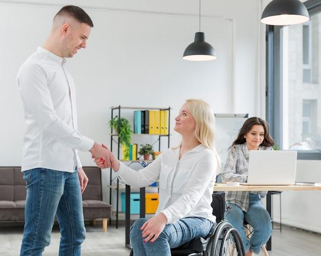 Mujer en silla de ruedas estrechándole la mano con un compañero de trabajo Foto gratis