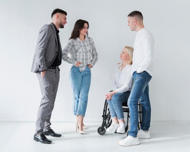 Mujer en silla de ruedas hablando con sus compañeros de trabajo Foto gratis
