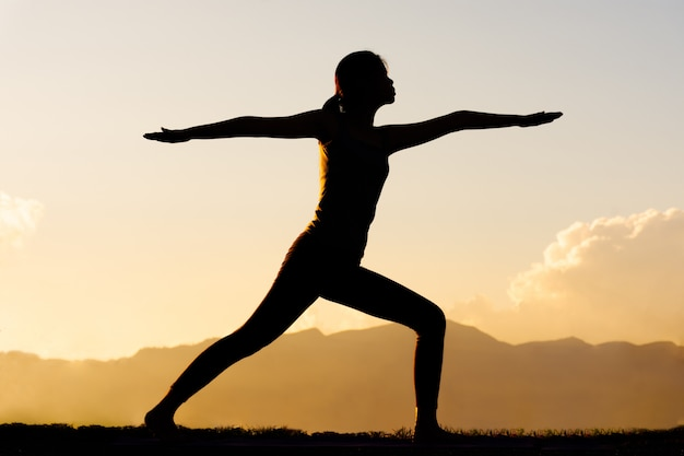 Mujer de silueta practicando yoga en la cima de la montaña Foto Premium