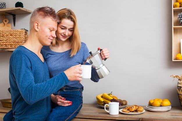 Mujer sirviendo a su novio un café con espacio de copia Foto gratis