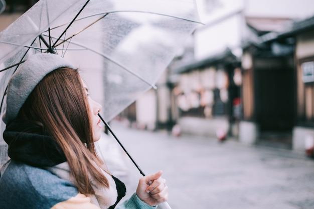 La mujer sola con el paraguas está esperando la lluvia en la calle en japón. Foto Premium