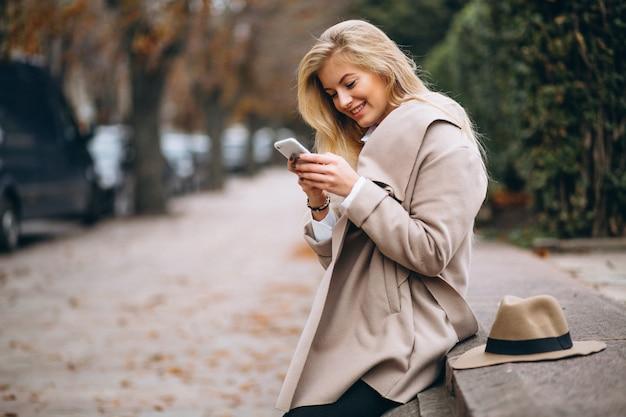 Mujer con sombrero y abrigo en el parque hablando por teléfono Foto gratis