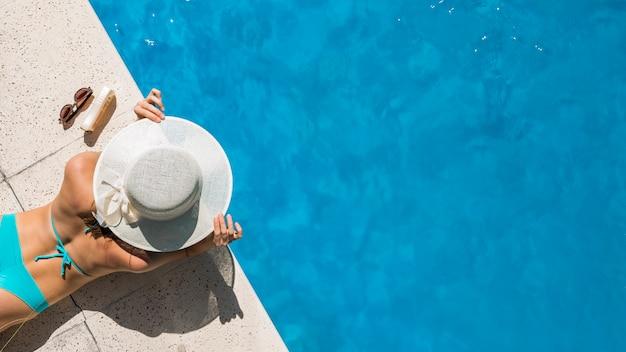 Mujer con sombrero de ala ancha acostada en el borde de la piscina Foto gratis