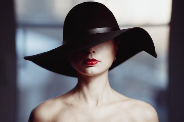 4f6093255c6fc Mujer con sombrero cubriendo sus ojos