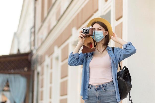 Mujer con sombrero y mascarilla tomando fotos Foto gratis