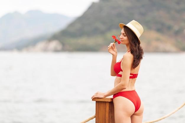 Mujer con sombrero que huele a flor Foto gratis