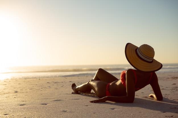 Mujer con sombrero relajante en la playa Foto gratis