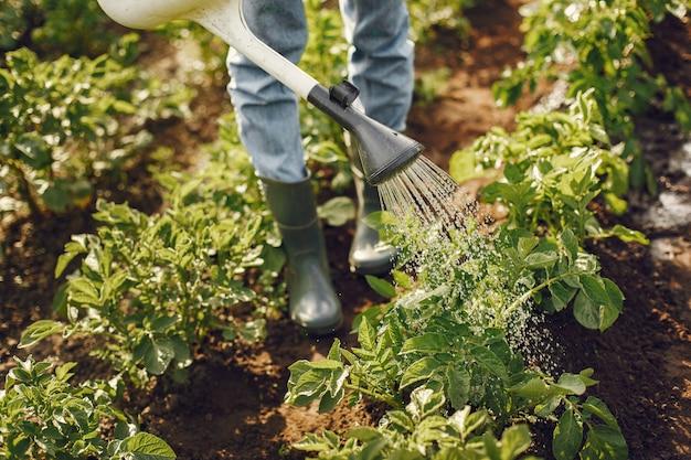Mujer con sombrero sosteniendo embudo y trabaja en un jardín. Foto gratis