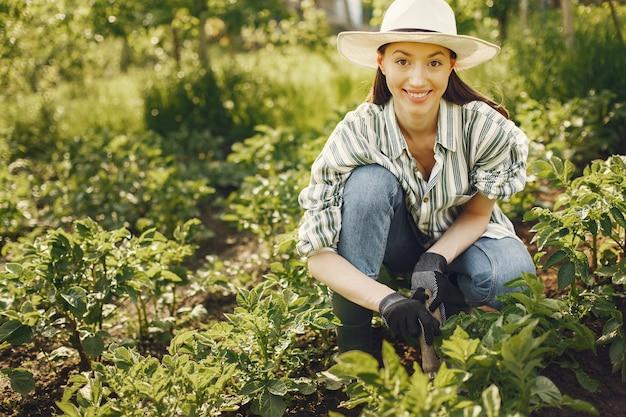 Mujer con sombrero trabajando en un jardín. Foto gratis
