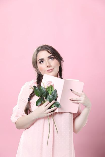 Mujer soñadora con rosas y libro Foto gratis