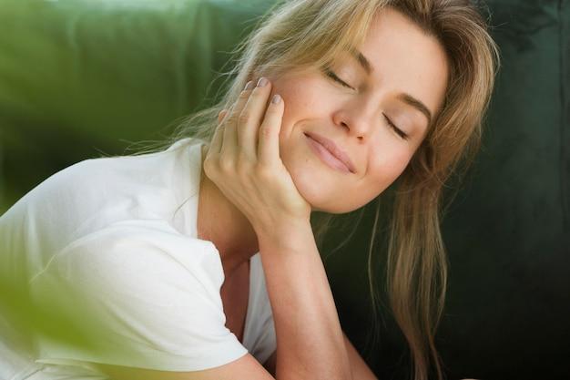 Mujer soñando despierta y planta borrosa Foto gratis