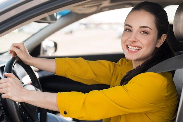 Mujer sonríe y sentada en el auto Foto gratis