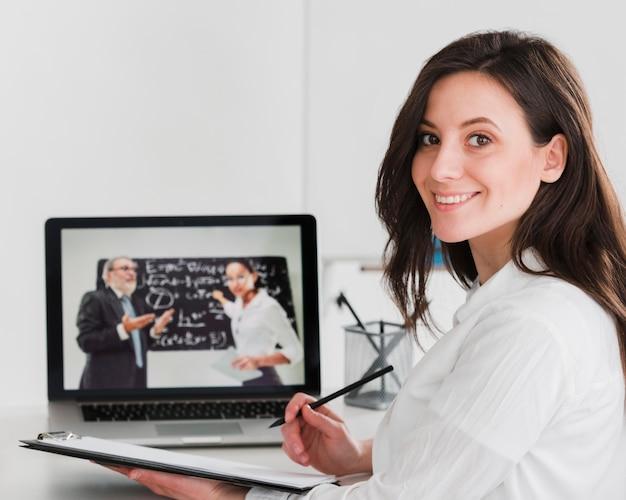 Mujer sonriendo y aprendiendo en línea desde la computadora portátil Foto Premium