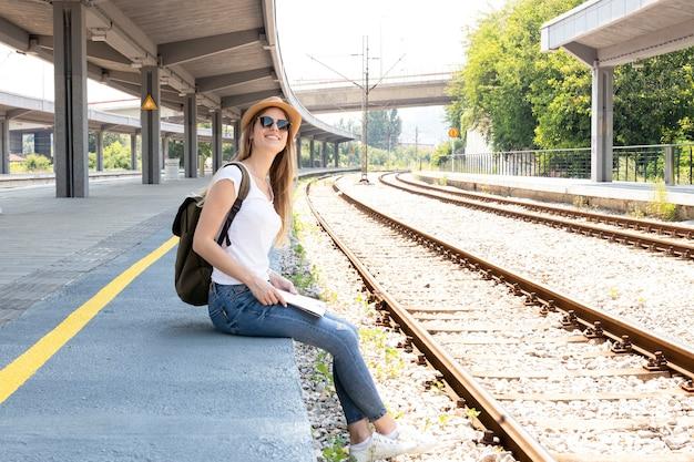 Mujer sonriendo y buscando el tren Foto gratis