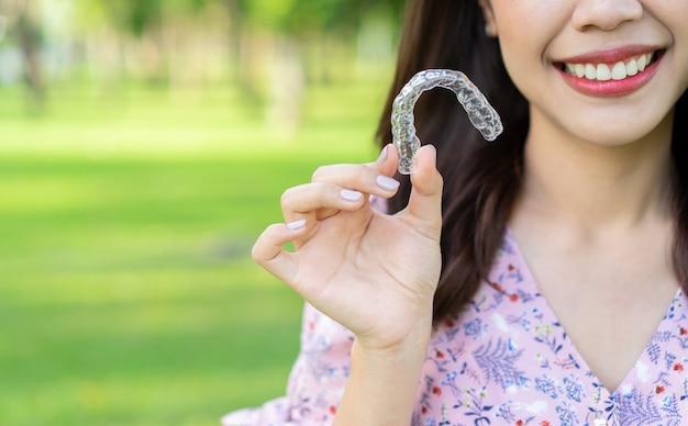 Mujer sonriendo con mano sujetador de alineador dental (invisible) en el parque natural al aire libre Foto Premium