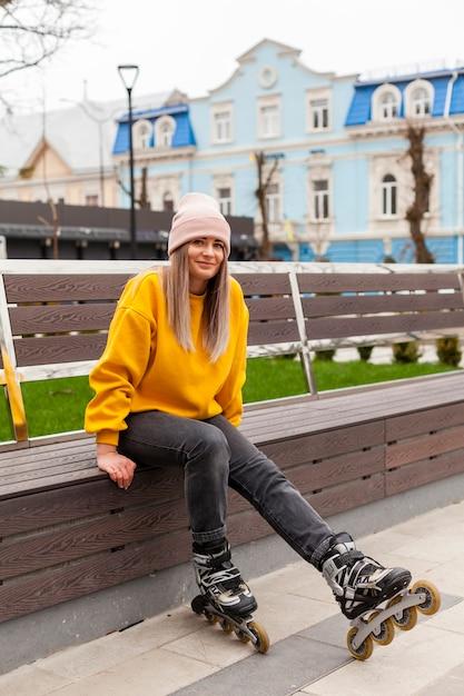 Mujer sonriendo y posando en un banco con patines Foto gratis