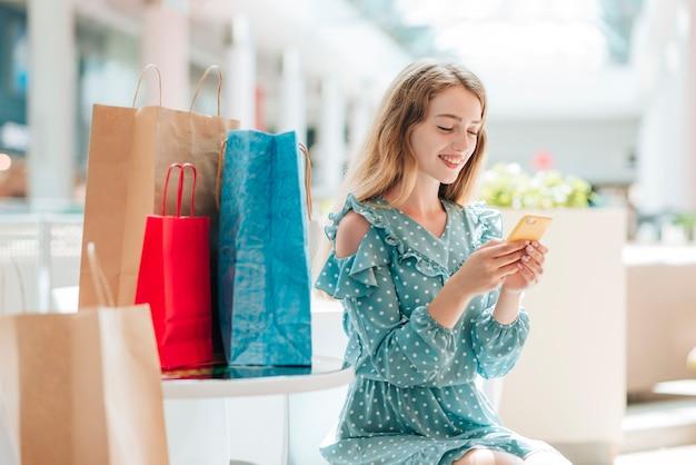 Mujer sonriendo y revisando su teléfono Foto gratis