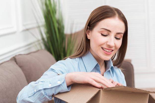 Mujer sonriente abriendo un paquete en el interior Foto gratis
