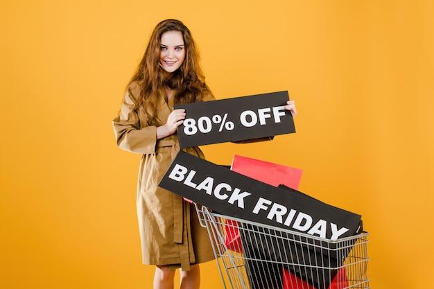 Mujer sonriente en abrigo de otoño con viernes negro 80% signo y coloridas bolsas de compras en carro aislado sobre amarillo Foto Premium